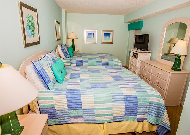 Another guest bedroom with two queen beds and flat screen tv.  A great space for all of the kids.