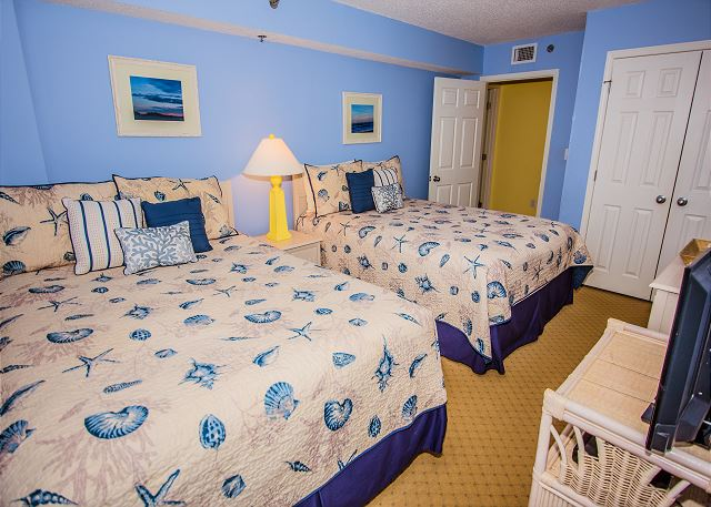 Guest room with two queens offers a tropical retreat.