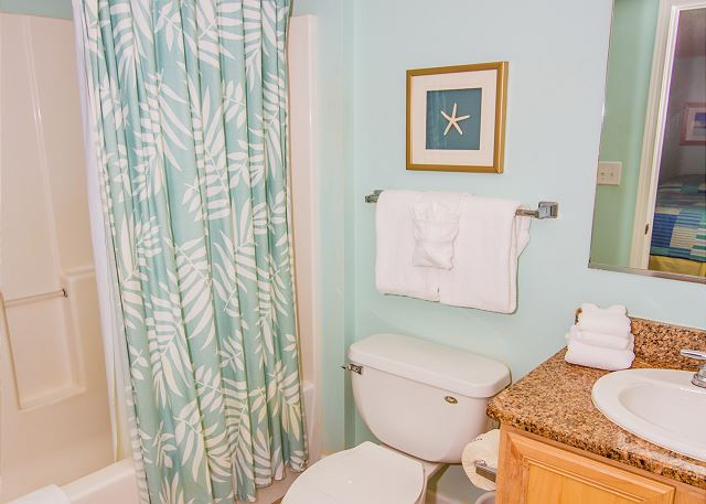 Guest bath colorfully decorated and bath linens provided.