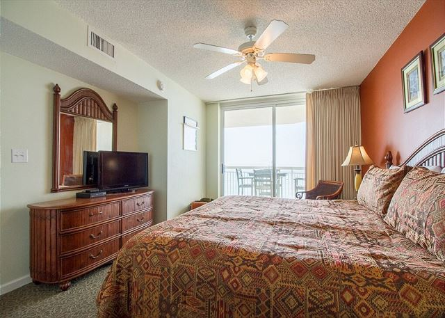Master Bedroom with a king size bed and sliding glass door to the ocean front balcony.