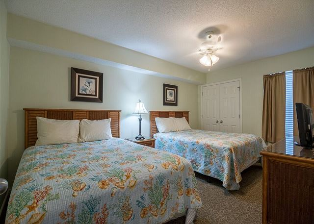 """-2 queen size beds, 26'"""" flat screen TV and DVD player, ceiling fan, a full length dresser with mirror, night stand, lamp, alarm clock, phone and a nice sized closet with hangers."""