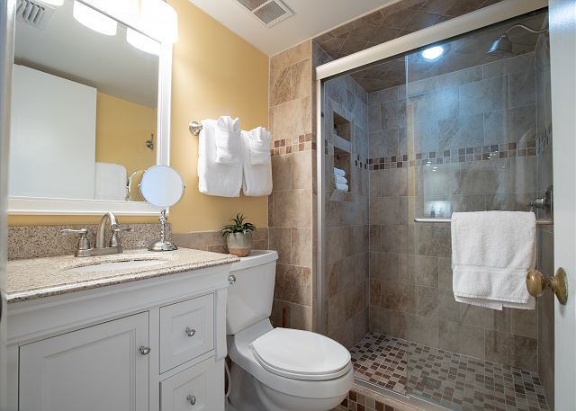 The bathrooms in this unit have also been updated. The same stylish tile found in the kitchen permeates the bathroom floor, half of the walls and the entire glass shower doors.  All new fixtures and hardware complete the look of this fantastic upgrade. .