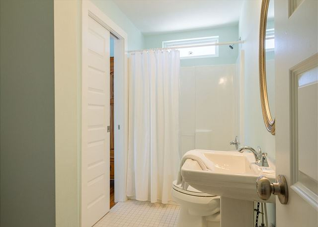 Upstairs shared bath with tub-shower combo.