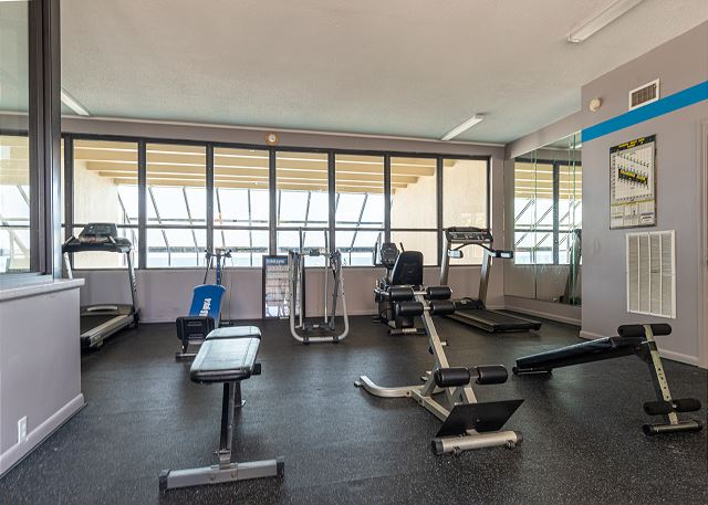 The fitness center has views upstairs over the indoor pool and through the glass wall, you can see the outdoor hot tub and the beach.