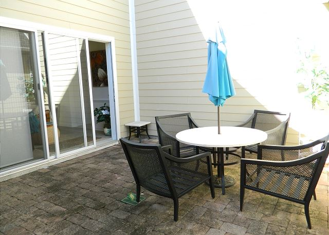 Private outdoor patio, with table and chairs for casual dining.