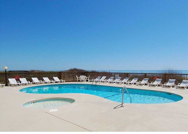 Outdoor pool and large sundeck with lounge chairs for hours of relaxation by the sea.