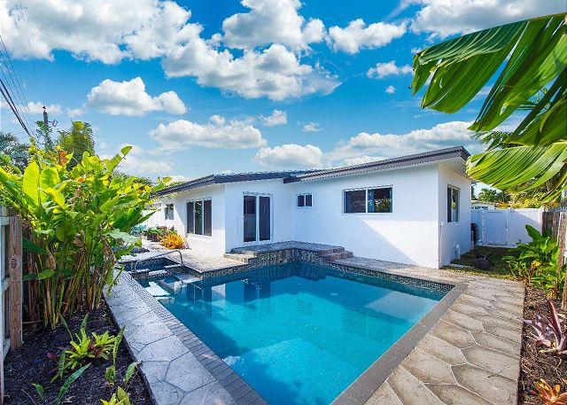 Luxurious private heated pool with tropical landscaping surrounding pool deck.