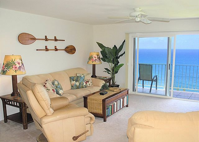 Ocean view living room with suede couch and chair and full leather easy chair.
