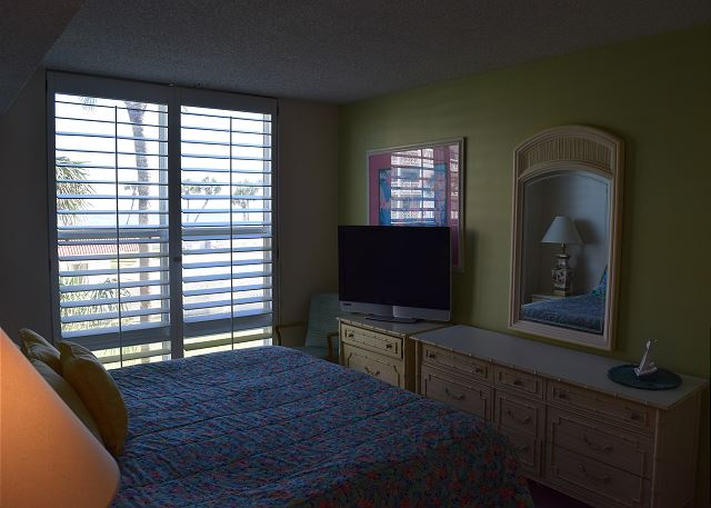 Master bedroom with a king sized bed and flat screen television.