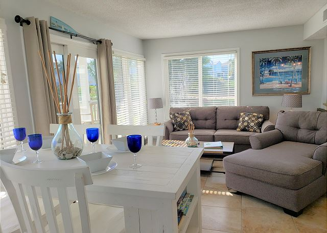 beautiful coastal dining and living area with access to the ground level patio