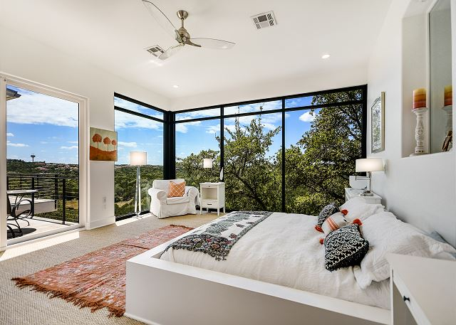 Restful master bedroom overlooking the lush hill country