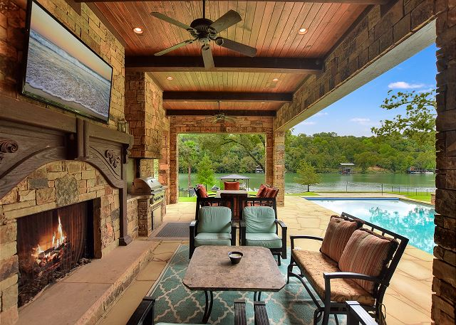 Outdoor living complete with seating, TVs, and fire place.