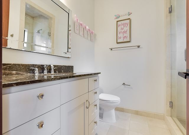 Full bathroom with marble counter tops.