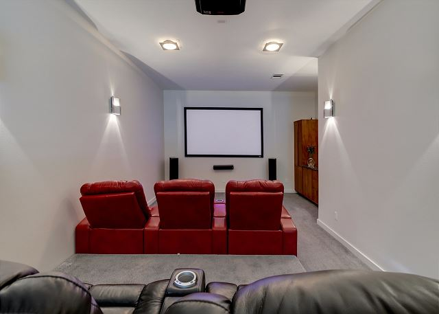 Have a fun family movie night in this media room with recliner seats and large projector screen