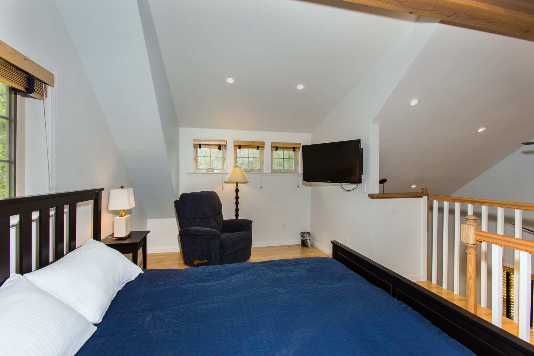 The upstairs sleeping loft with a queen bed and flatscreen tv