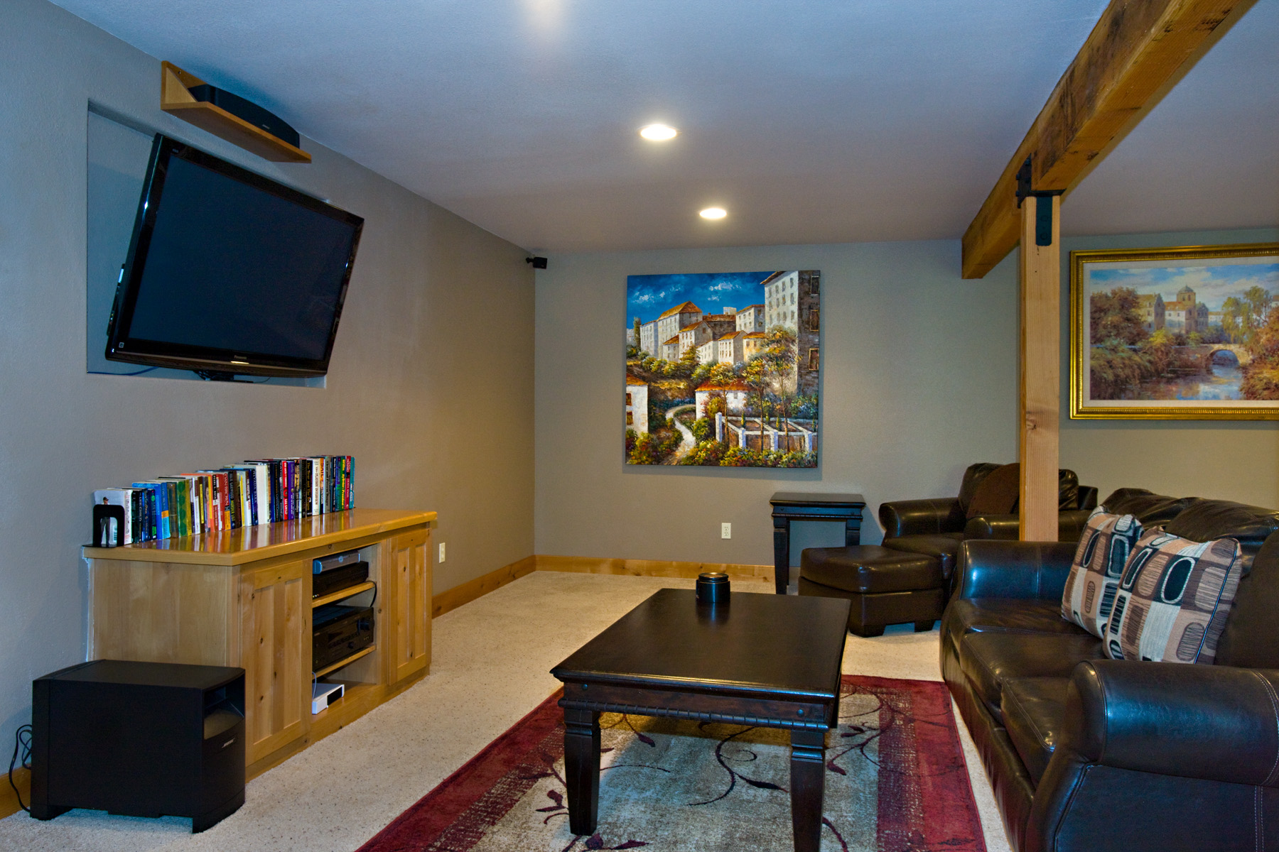 The downstairs media room with large flat screen TV, leather sof