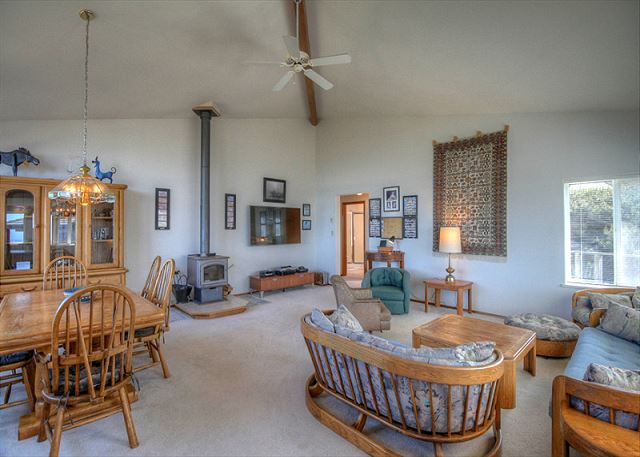 Living room view from West to East, Wood burning stove, flat screen and entrance to bedroom areas.