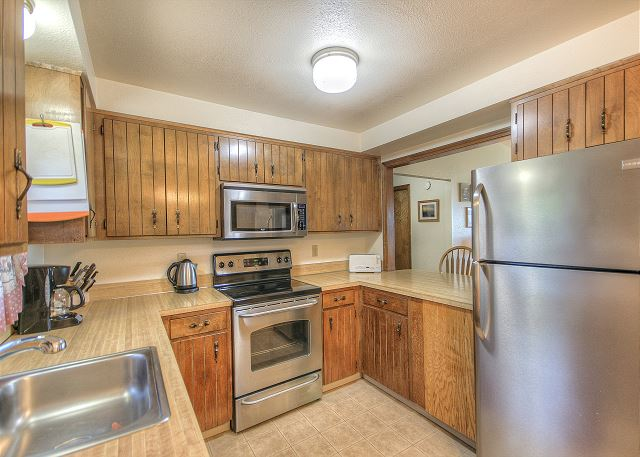 Kitchen with breakfast bar. Stove, microwave, coffee pot, hot water pot. Everything you need for enjoying meals at home.