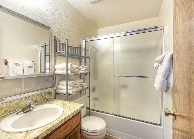 Shower/tub combination in full bath located in the hallway between two queen bedrooms