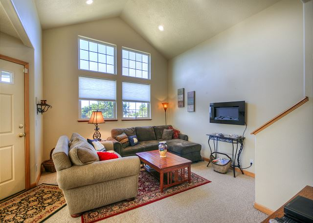 Cozy livingroom with electric fireplace. Tall vaulted ceiling windows brighten up the room daily.