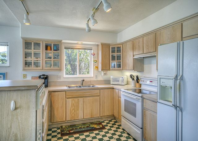 Kitchen with microwave, side by side refrigerator, microwave and keurig coffee pot. Dishwasher and breakfast bar area.