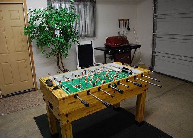 Foos ball table with dart board in the garage.