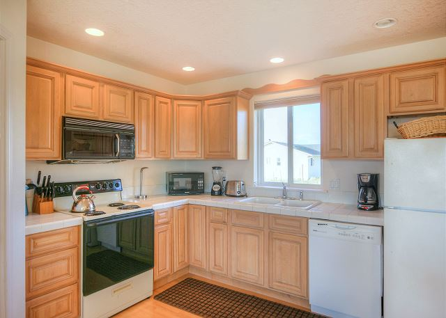Beautiful kitchen with everything you need for cooking. Coffee maker, blender, microwave, range and dishwasher.