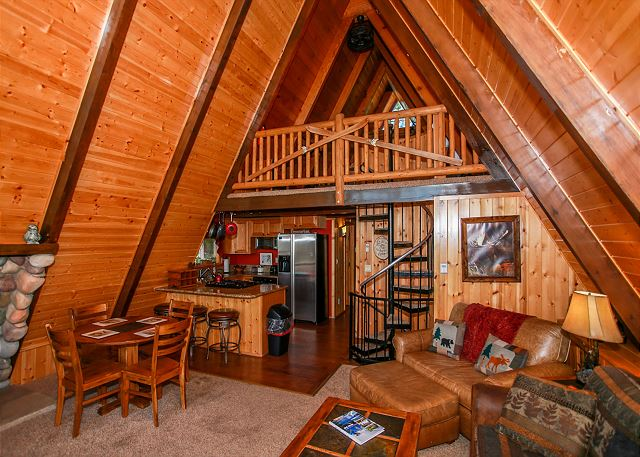 View of first floor, upper loft area and stairs leading down to other part of the cabin