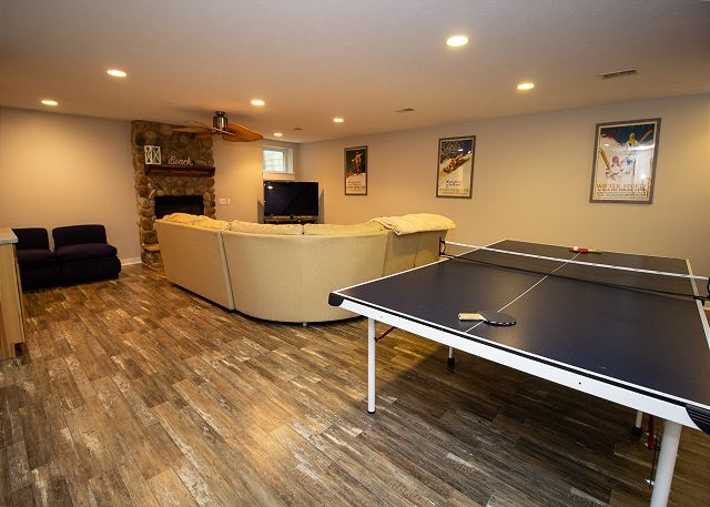 Basement Level with sleeper sofa and ping pong table
