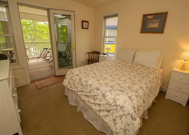 Second level bedroom 4 queen bed with door to screened in porch