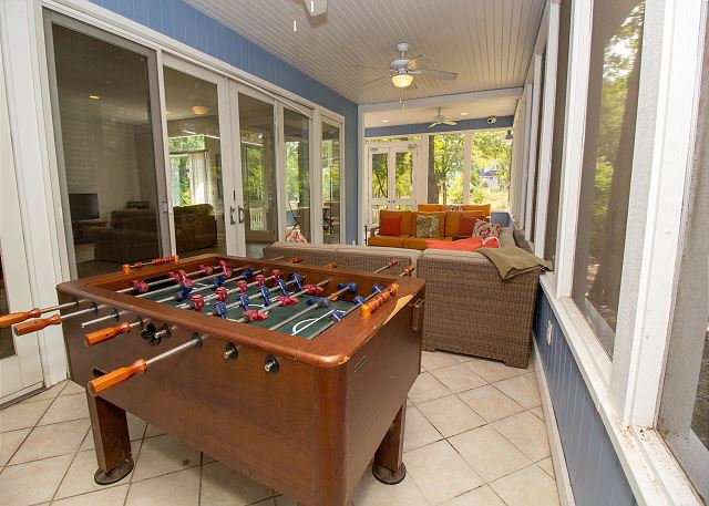 Main level screened in porch with foosball table