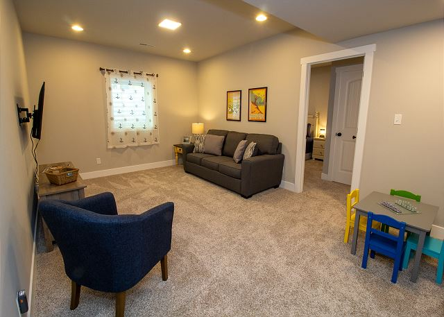 Basement living area with a kids corner and sleeper sofa