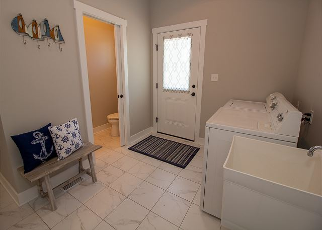 Off the kitchen is the laundry room with a half bath