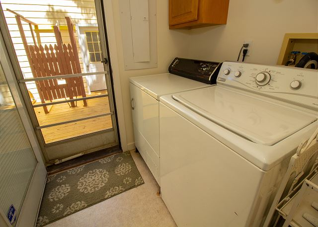 Main level washer and dryer with a door to the back deck and gri
