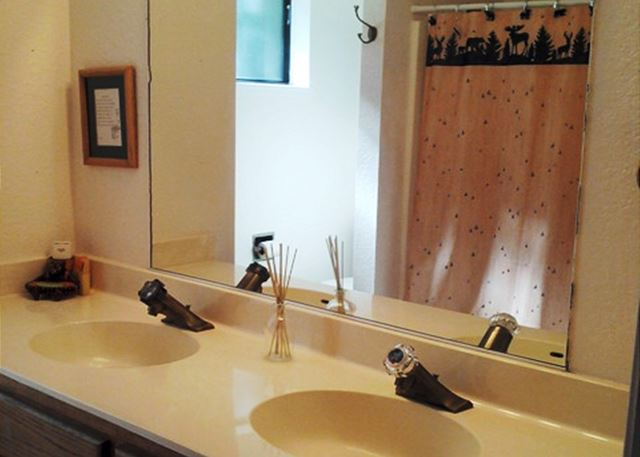 Downstairs full bath has dual vanities.