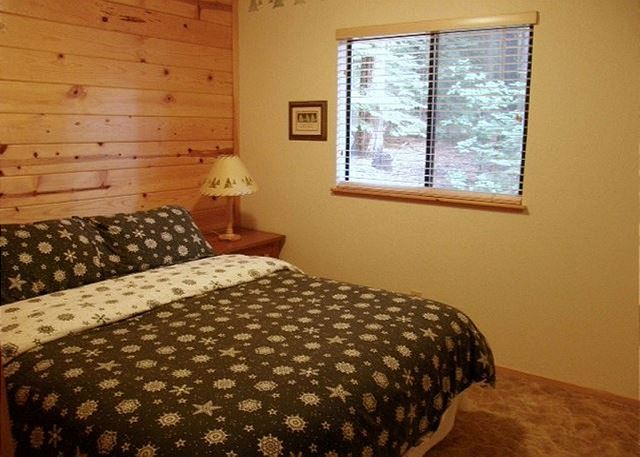 This bedroom located on the main floor offers yet another beautiful view of the forest.