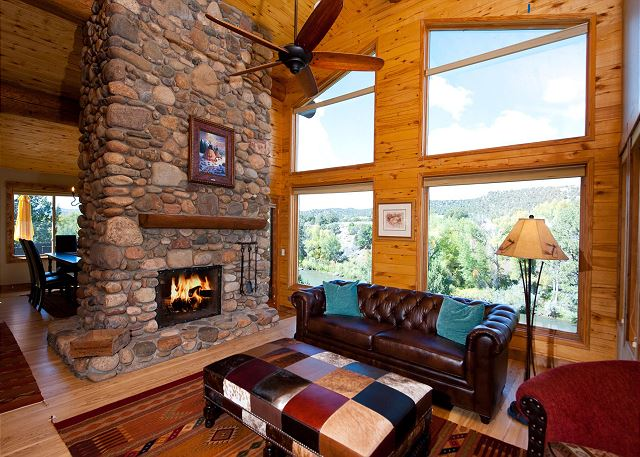 Living room with fireplace, TV, and ceiling fan