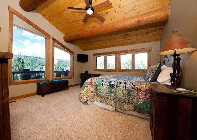 Master bedroom with king size bed, TV, and ceiling fan