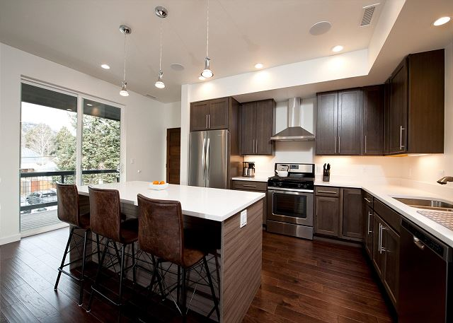 Kitchen with traditional drip coffee maker, fridge, stove, and oven. Island with bar stools.