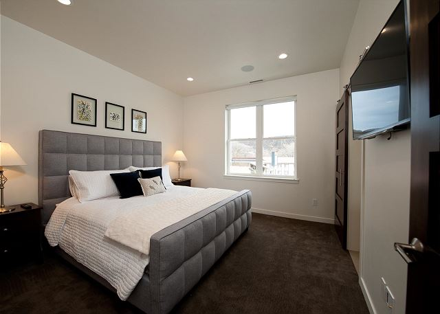 Master bedroom with king size bed and TV