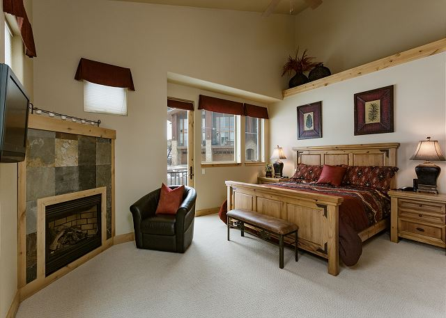 Master bedroom with king size bed, fireplace and TV