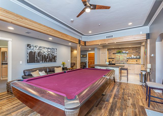 Living room with pool table looking into kitchen