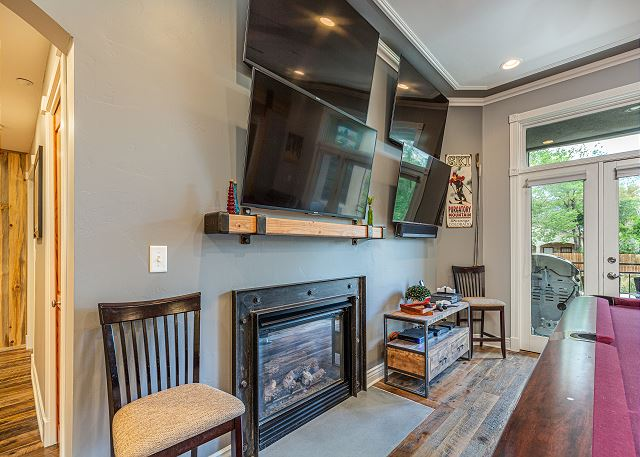 Living room with fireplace and four TVs to watch sports games