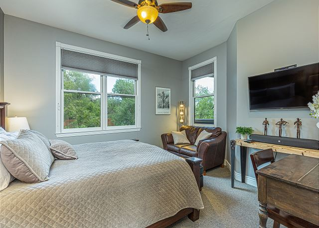 Bedroom with king size bed, ceiling fan, and television