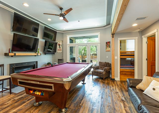 Living room with ceiling fan, pool table, and four televisions to watch sports games