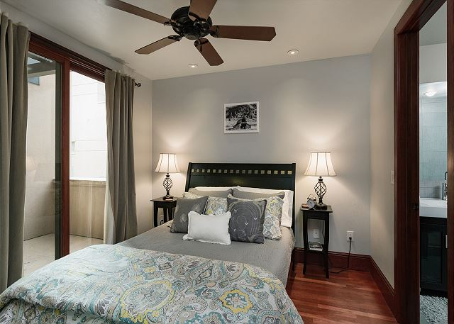 Master bedroom with queen, TV and ceiling fan