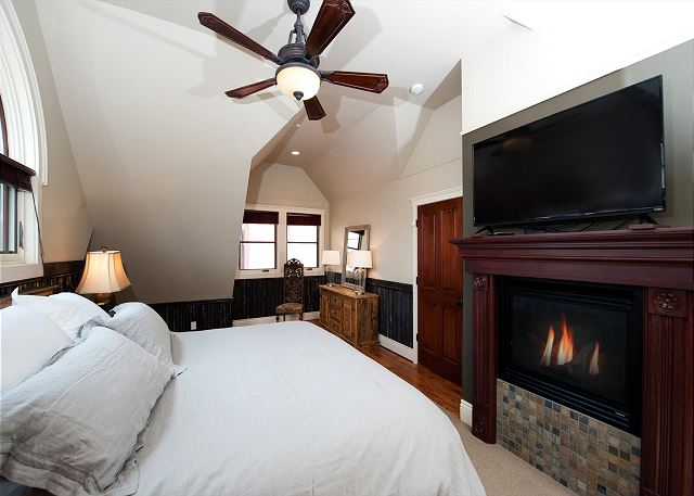 Master bedroom with ceiling fan, fireplace, and TV