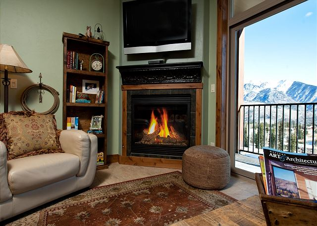 Living room with tv and fireplace. Access to patio with mountain views.