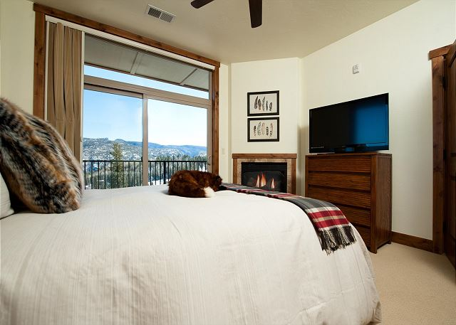 Master bedroom with ceiling fan, fireplace, and access to back patio with mountain views.  Bed size: Queen