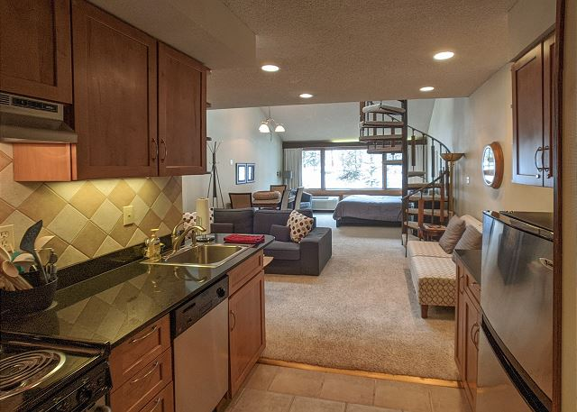 One bedroom condo with queen bed on main level, two twins in the loft, kitchen, and spiral staircase to the loft.